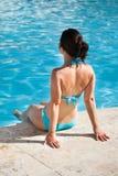 Frau, die am Rand des Swimmingpools sitzt Lizenzfreie Stockfotos