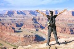 Frau, die am Rand einer Klippe mit den Händen oben steht Stockbild
