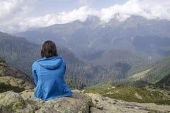 Frau, die am Rand einer Klippe sitzt und auf einem Berg L schaut Lizenzfreies Stockfoto