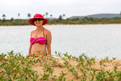 Frau, die Red Hat auf dem Strand trägt Stockfotos