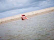 Frau, die Red Hat legt auf den Strand trägt Stockfotografie