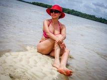 Frau, die Red Hat sitzt auf Strand trägt Stockbild