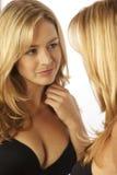 Frau, die Reflexion im Spiegel betrachtet Lizenzfreie Stockfotografie