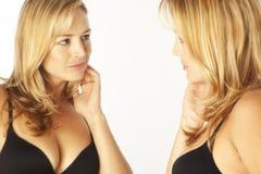 Frau, die Reflexion im Spiegel betrachtet Lizenzfreie Stockbilder