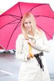 Frau, die Regenschirm im Regen hält Stockbild