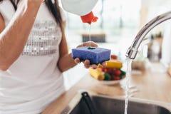 Frau, die Reiniger zu einem Schwamm setzt Händewaschenteller stockbilder