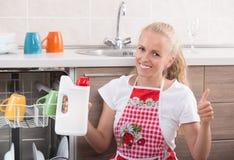 Frau, die Reinigungsmittel für Spülmaschine zeigt Lizenzfreies Stockfoto