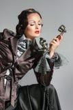 Frau, die am Retro- Telefon spricht Stockfotos