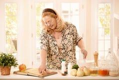 Frau, die Rezept in der Küche überprüft Lizenzfreies Stockbild