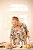 Frau, die Rezept in der Küche überprüft Lizenzfreie Stockfotos