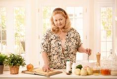 Frau, die Rezept in der Küche überprüft Stockfotos