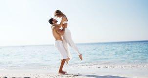 Frau, die in Richtung zum Mann läuft und in seine Arme am Strand 4k springt stock video