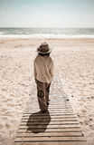 Frau, die in Richtung zum Meer auf Promenade geht stockbilder