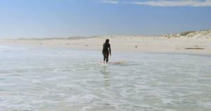 Frau, die in Richtung zum Surfbrett auf dem Meer 4k läuft stock video