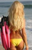 Frau, die in Richtung zum Wasser mit Flossen geht Stockfoto