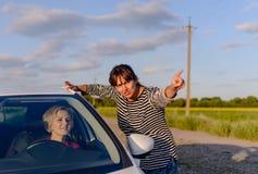 Frau, die Richtungen zu einem verlorenen Fahrer gibt Stockfotografie