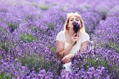 Frau, die an riechenden Blumen des Lavendelfeldes sitzt Lizenzfreie Stockfotografie