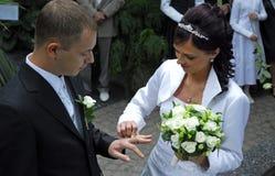 Frau, die Ring auf Bräutigam setzt Stockfotografie