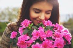Frau, die rosa Blumen riecht Stockfoto