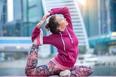Frau, die rosa Sportkleidung in einer mit Beinen versehenen Haltung Königs Pigeon trägt Stockbild