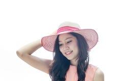 Frau, die rosa Strohhut mit Ausdruck von glücklichem trägt stockfoto