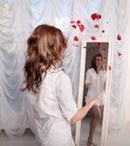 Frau, die rosafarbene Blumenblätter nahe dem Spiegel wirft stockfotos