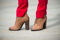 Frau, die rote Hosen und braune lederne Schuhe des hohen Absatzes in der alten Stadt trägt Stockfoto