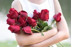 Frau, die rote Rosen mit Vergnügen umarmt Lizenzfreies Stockfoto