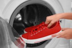 Frau, die rote Turnschuhe in Waschmaschine setzt stockfotografie