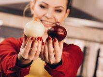 Frau, die rote und weiße Zwiebel hält lizenzfreies stockfoto