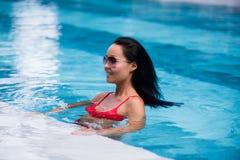 Frau, die roten Badeanzug und die Sonnenbrille sitzt im Swimmingpool, rührendes nasses Haar trägt Stockfotografie