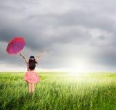 Frau, die roten Regenschirm im grünen Gras und im Regen anhält Stockbild