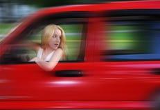 Frau, die rotes Auto mit Drehzahl antreibt Lizenzfreie Stockfotos