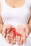 Frau, die rotes Farbband zur Unterstützungs-AIDS-Ursache zeigt Lizenzfreies Stockbild