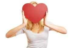 Frau, die rotes Herz in der Front hält Stockfoto