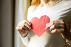 Frau, die rotes Papierherz hält Liebes- und Valentinsgrußtageskonzept Lizenzfreies Stockbild
