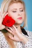 Frau, die Rotrosenblume auf Blau hält Lizenzfreie Stockfotos