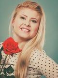 Frau, die Rotrosenblume auf Blau hält Stockfotos