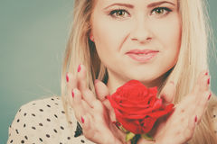 Frau, die Rotrosenblume auf Blau hält Lizenzfreie Stockfotografie