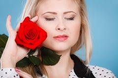 Frau, die Rotrosenblume auf Blau hält Lizenzfreies Stockfoto