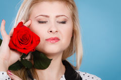Frau, die Rotrosenblume auf Blau hält Lizenzfreies Stockbild
