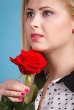 Frau, die Rotrosenblume auf Blau hält Stockfotografie