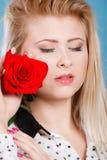 Frau, die Rotrosenblume auf Blau hält Stockbilder