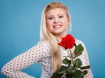 Frau, die Rotrosenblume auf Blau hält Stockbild
