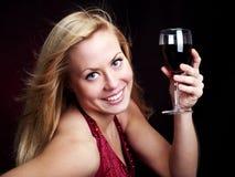 Frau, die Rotwein über Dunkelheit anhält Stockbild
