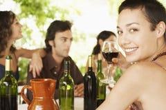 Frau, die Rotwein mit Freunden im Hintergrund genießt Lizenzfreie Stockfotos