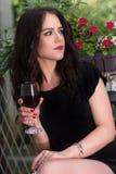Frau, die Rotweinglas in der Hand hält und im Gartenpark sich entspannt stockfotografie