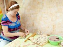 Frau, die russische Fleischmehlklöße bildet Lizenzfreies Stockfoto