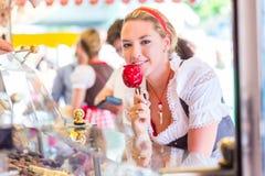 Frau, die Süßigkeitsapfel bei Oktoberfest oder bei Dult isst Stockfoto