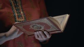 Frau, die ` s übergibt, hält den Koran - Heilige Schrift von Moslems stock video
